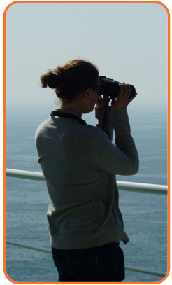 A Marine Mammal Observer (MMO) surveying animals in the North Sea. © OSC 2013.